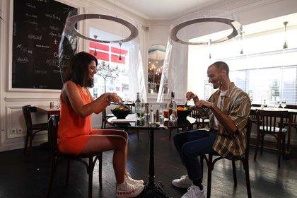 Una pareja almuerza en un restaurante de París, separados por protectores de plexiglass (27 de mayo)