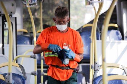 Un chofer higieniza un colectivo, en medio de las restricciones impuestas en Uruguay por el coronavirus (EFE)