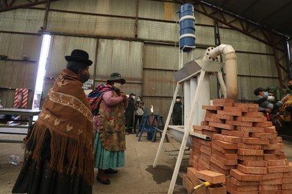 """Ciudadanos alteños fueron registrados este miércoles al observar el """"microreactor de conversión de la basura en diésel"""", durante su presentación en la planta piloto de metalurgia Heresi, en la zona Nuevo Amanecer de El Alto (Bolivia). EFE/Martín Alipaz"""
