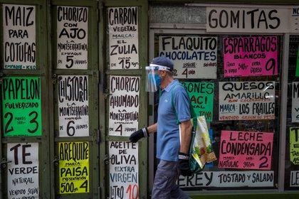 Un hombre camina frente a una vitrina de la que cuelgan carteles con precios de alimentos el 15 de octubre de 2020, en Caracas (EFE/ Miguel Gutiérrez)