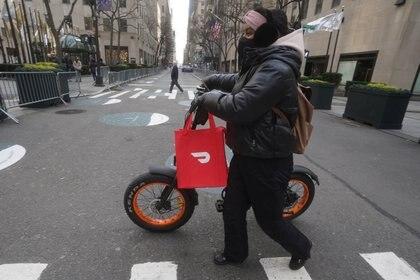 Un repartidor de DoorDash, fundada en 2013 por 3 chino-americanos, cuya salida a la bolsa la cotizó en USD 70.000 millones  REUTERS/Carlo Allegri
