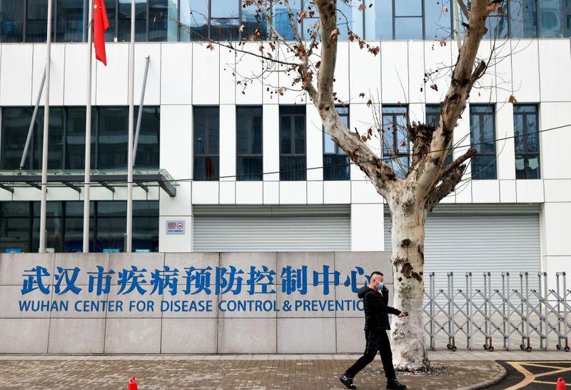 Foto del lunes dde un hombre con mascarilla pasando frente a la sede del CDC de Wuhan, en China  Feb 1, 2021. REUTERS/Thomas Peter