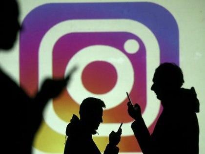 Imagen de archivo de siluetas de usuarios de teléfonos móviles junto a una pantalla que muetra una proyección del logo de Instagram en esta fotografía ilustrativa tomada el 28 de marzo, 2018. REUTERS/Dado Ruvic/Ilustración/Archivo