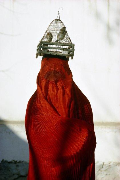 Una mujer vestida con un chadri rojo (una vestimenta tradicional islámica para cubrirse), lleva jilgueros sobre su cabeza en Kabul, Afganistán. Thomas J. Abercrombie, 1968