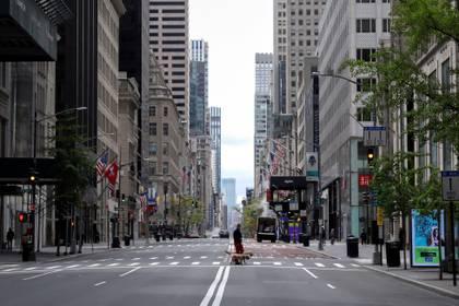 Un hombre pasea perros a través de una 5ta Avenida casi vacía y de tiendas de lujo cerradas, el 11 de mayo de 2020 (REUTERS/Mike Segar)