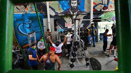 """ACOMPAÑA CRÓNICA: MÉXICO REINSERCIÓN AME6983. NAUCALPAN (MÉXICO), 08/08/2020.- Jóvenes hacen ejercicio en el gimnasio Barras Praderas, el 7 de agosto de 2020 en el municipio de Naucalpan (México). Aun con una sola pierna, Paul Villafuerte entrena duro en Barras Praderas. En Naucalpan, Estado de México, uno de los municipios con más delincuencia en la entidad, se ubica este gimnasio callejero """"sui generis"""" que promueve la actividad física para rescatar a niños y jóvenes de las drogas y la delincuencia. EFE/Jorge Núñez"""