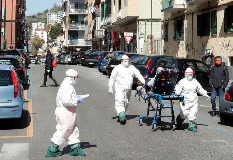 Personal médico con trajes protectores traslada a un paciente con coronavirus en Nápoles. (REUTERS/Ciro De Luca)