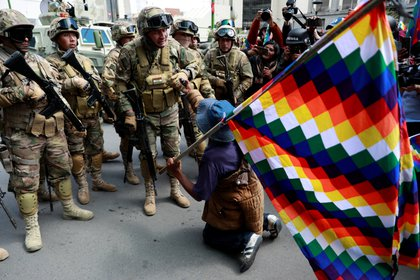 Un hombre sosteniendo una bandera wiphala se arrodilla ante un militar en La Paz, Bolivia (REUTERS/Henry Romero)