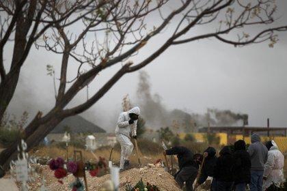 Empleados funerarios sepultan a personas fallecidas por la covid-19 este martes, en el cementerio San Rafael en la fronteriza Ciudad Juárez, estado de Chihuahua. EFE/Luis Torres