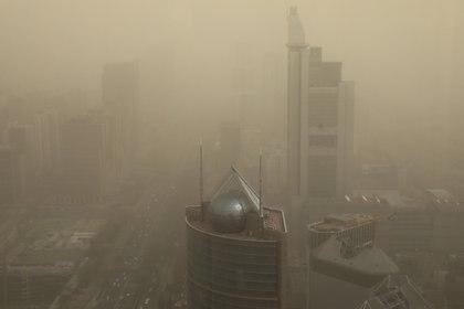 Una vista general de la ciudad envuelta en smog después de una tormenta de arena, en el centro de Beijing. REUTERS/Tingshu Wang
