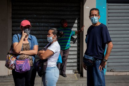 Personas hacen fila para comprar en una tienda, en Caracas (Venezuela). EFE/Rayner Peña/Archivo