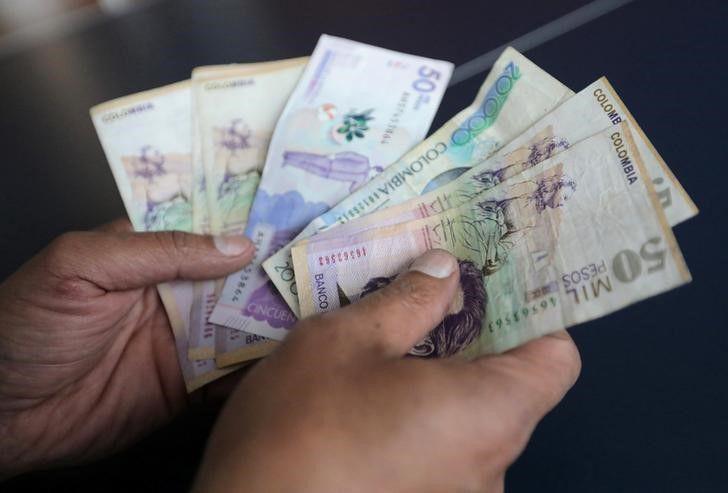 Foto de archivo ilustrativa de un empleado de una tienda en Colombia contando dinero.  Dic 28, 2018. REUTERS/Luisa Gonzalez