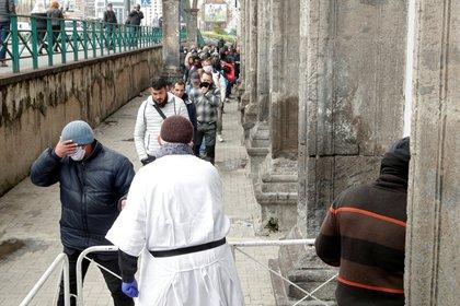 El sacerdote Francesco con una máscara facial y guantes protectores, entrega bolsas de comida a personas sin hogar y pobres, mientras continúa la propagación de la enfermedad por coronavirus (COVID-19), en Nápoles, Italia, el 27 de marzo de 2020. (REUTERS / Ciro De Luca)