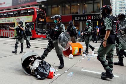 Un policía antidisturbios patea un tacho de basura arrojado por manifestantes en Hong Kong (REUTERS/Tyrone Siu)