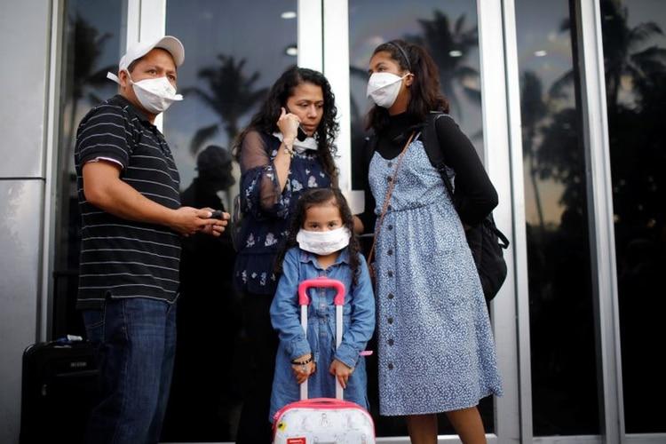 Imagen de archivo. Una familia de viajeros reaccionó a las medidas cada vez más estrictas del gobierno salvadoreño para prevenir una posible propagación del coronavirus (COVID-19), en el Aeropuerto Internacional Saint Oscar Romero en San Luis Talpa, El Salvador. 16 de marzo de 2020. REUTERS / Jose Cabezas