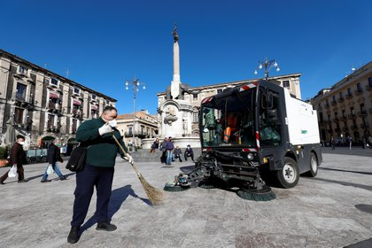 Trabajadores limpian una plaza después de una impresionante erupción volcánica del Monte Etna en Catania, Italia, el 17 de febrero de 2021. REUTERS / Antonio Parrinello