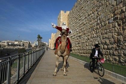 Un hombre judío ultraortodoxo pasa en bicicleta por delante de Issa Kassissieh disfrazado de Papá Noel después de repartir árboles de Navidad en las afueras de la Ciudad Vieja de Jerusalén  (REUTERS/Ammar Awad)