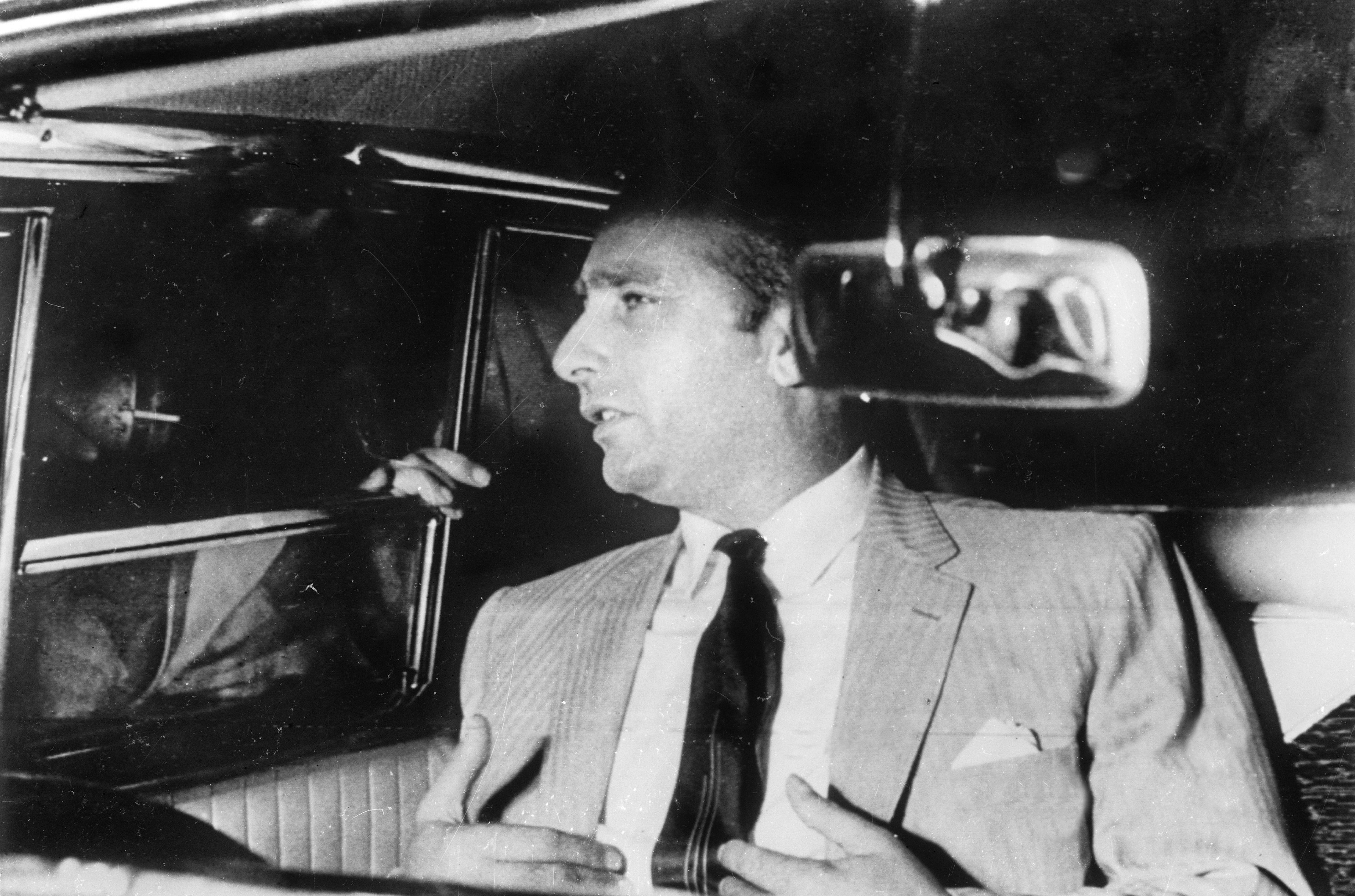 Juan Manuel Fangio, en el coche del embajador argentino en Cuba, Raúl Lynch Guevara, habla con los periodistas a su llegada a la embajada argentina en el barrio de Miramar, después de su liberación (EFE)