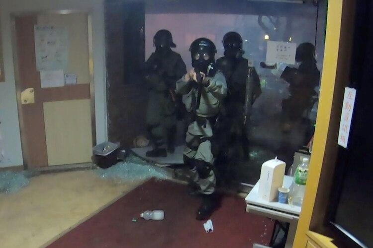 La Policía antidisturbios en el momento de irrumpir en el sector de la radio de la PolyU de Hong Kong (PolyU Campus Radio/via REUTERS)