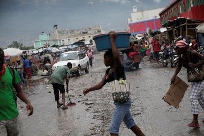 Un hombre barre una calle después de las lluvias por el paso de Isaías, que se convirtió en huracán después, en Puerto Príncipe, Haití (REUTERS/Andrés Martínez Casares)