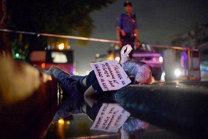 """El cuerpo de un hombre, con la cabeza envuelta en cinta adhesiva, se encuentra en una cuneta de Manila. La nota manuscrita atada a su cabeza dice en filipino: """"Soy un ladrón crónico. Es mejor cambiar!"""" (Reuters)"""