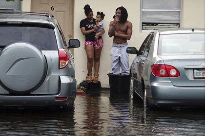 Evan y Denise Knight intentan mantenerse secos con su hijo Zion en una calle inundada de Melrose Park en Fort Lauderdale. (Joe Cavaretta/South Florida Sun-Sentinel via AP)