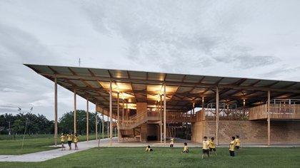 LaAldea de los Niños – por Aleph Zero y Marcelo Rosenbaum – es un modelo de ingenio arquitectónico en una remota región rural de Brasil. La misma ofrece alojamiento para 540 alumnos. Los dos edificios idénticos consisten en un gran techo apoyado en un bosque de esbeltas columnas de madera. Las pequeñas habitaciones están diseñadas con paredes perforadas y transpirables, lo que permite una ventilación cruzada natural (Estudio Gustavo Utrabo)