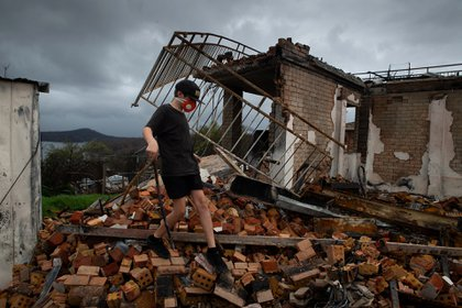 """Riley Fletcher, 12, walks on the ruins of his family's home in Conjola Park, Australia on Feb. 16, 2020. He is wearing a mask to protect himself from asbestos. Devastating floods came soon after the bush fires in Australia as  scientists call it """"compound extremes,"""" as one climate disaster intensifying the next. (Matthew Abbott/The New York Times)"""