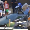 Military staff wearing protective masks serves a ration of food aid, organized by the municipality for a low-income neighborhood, during the mandatory quarantine for coronavirus disease (COVID-19), in Quilmes, on the outskirts of Buenos Aires, Argentina March 23, 2020