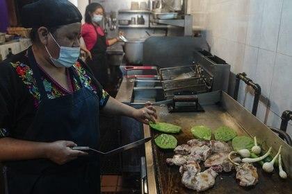 Natalia Méndez prepara una comida con chuletas de cerdo, jalapeños y nopales en la cocina de La Morada, un restaurante mexicano galardonado del que es copropietaria con su familia en el sur del Bronx, el miércoles 28 de octubre de 2020, en Nueva York (AP Foto/Bebeto Matthews)