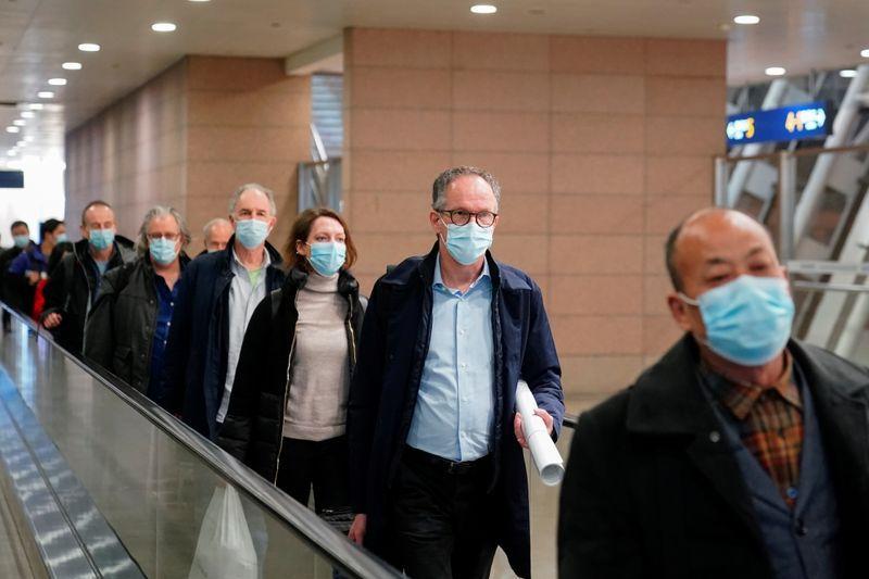 Peter Ben Embarek y otros miembros del equipo de la Organización Mundial de la Salud (OMS) encargado de investigar los orígenes de la enfermedad del coronavirus (COVID-19) llegan al aeropuerto internacional de Pudong en Shanghái, China. 10 de febrero de 2021. REUTERS/Aly Song