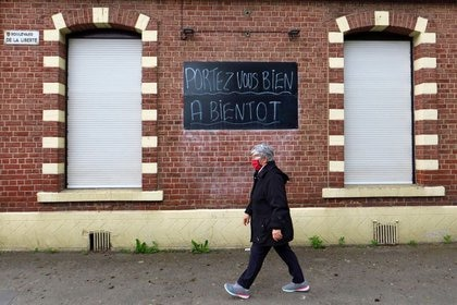 """Una mujer camina frente a un bar cerrado con un letrero que dice """"Pórtese bien, nos vemos"""", durante el confinamiento para desacelerar la propagación del COVID-19, la enfermedad que causa el coronavirus, en Cambrai, Francia. 3 de mayo, 2020. REUTERS/Pascal Rossignol"""