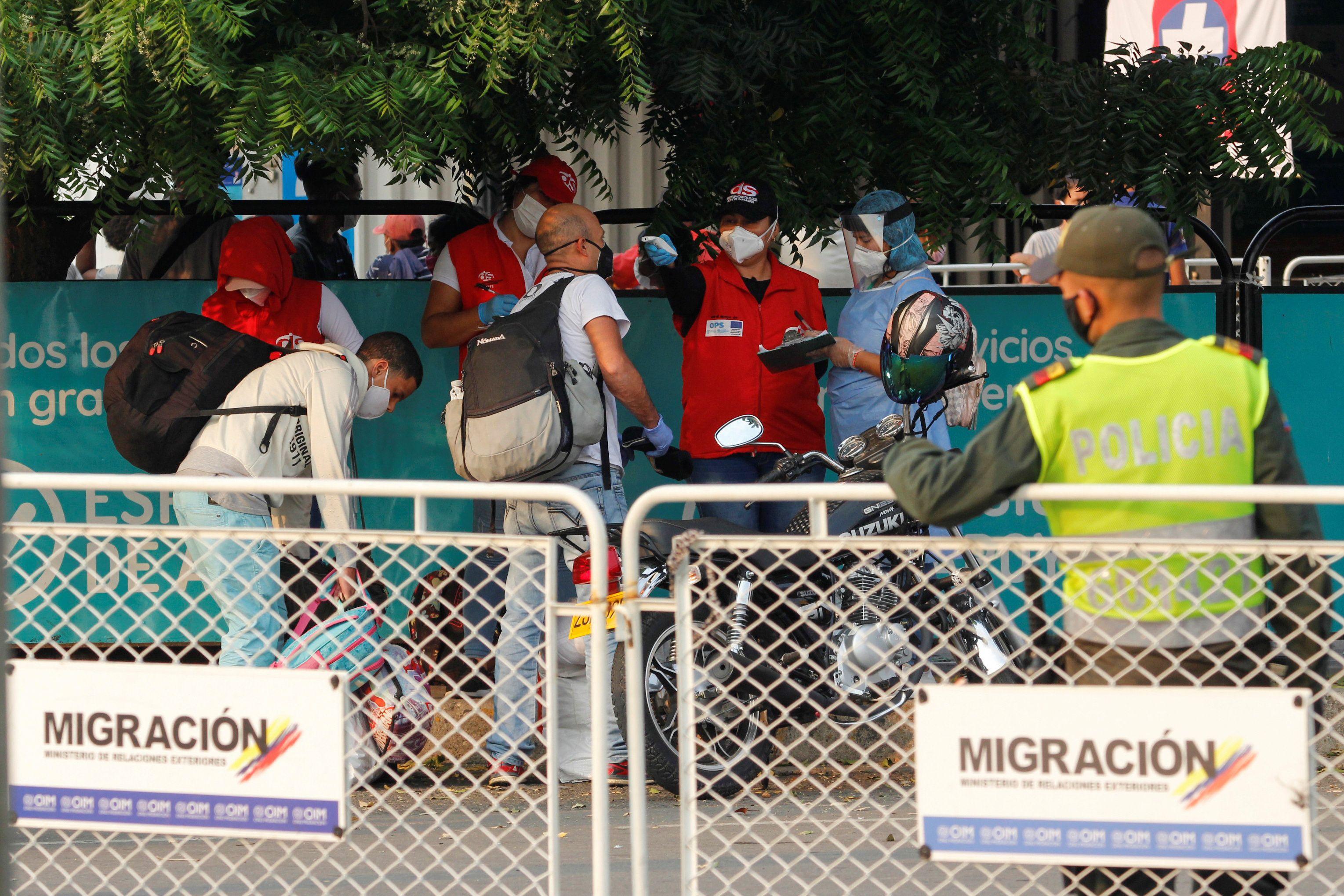 Oficiales revisan la temperatura de un grupo de venezolanos en el Puente Simón Bolívar antes de salir del territorio colombiano (Reuters)