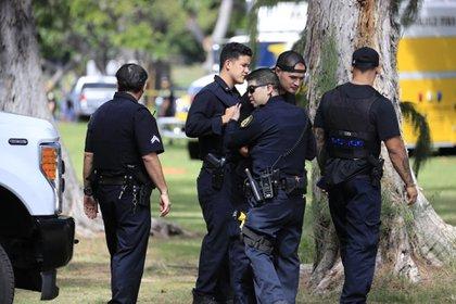 Compañeros de los policías asesinados en Honolulu, Hawaii, en la escena del hecho (AP)
