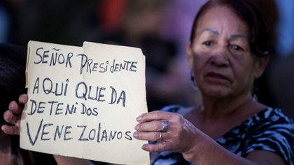 Una mujer muestra un cartel en el que hace un pedido a Maduro (EFE)