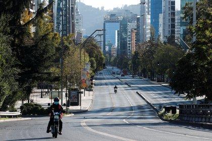 Un motociclista transita por una avenida casi vacía durante la cuarentena obligatoria decretada en prácticamente todo el país ante el avance de la pandemia, en Santiago, Chile (EFE/Alberto Valdés)