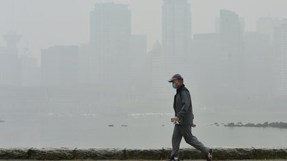A man wearing a face mask walks as smoke from wildfires in neighbouring Washington state shrouds Vancouver's skyline at Stanley Park in Vancouver, British Columbia, Canada September 14, 2020. REUTERS/Jennifer Gauthier