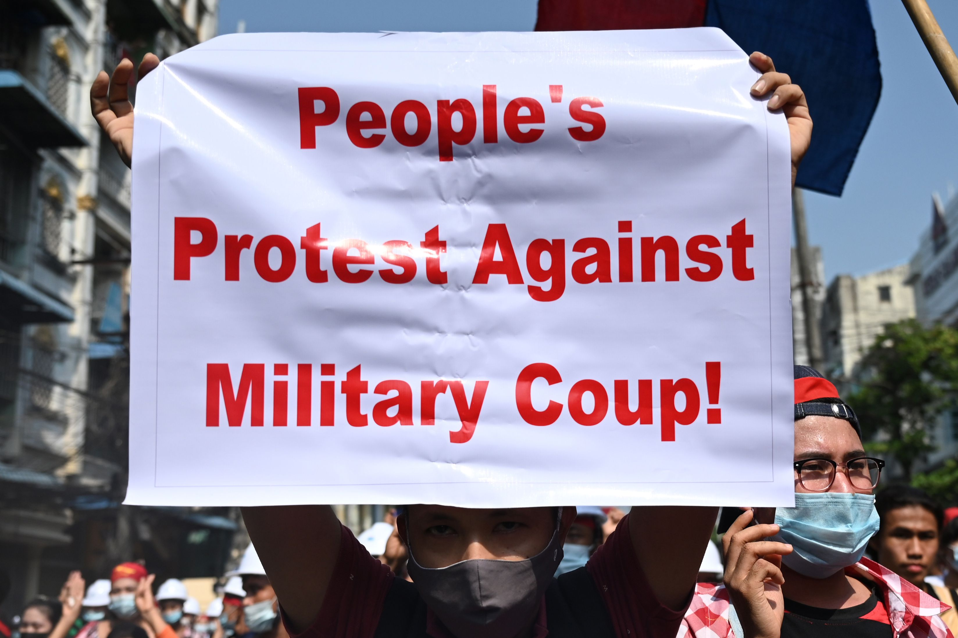 A protester holds up a sign during a demonstration against the military coup in Yangon on February 6, 2021. (Photo by YE AUNG THU / AFP)