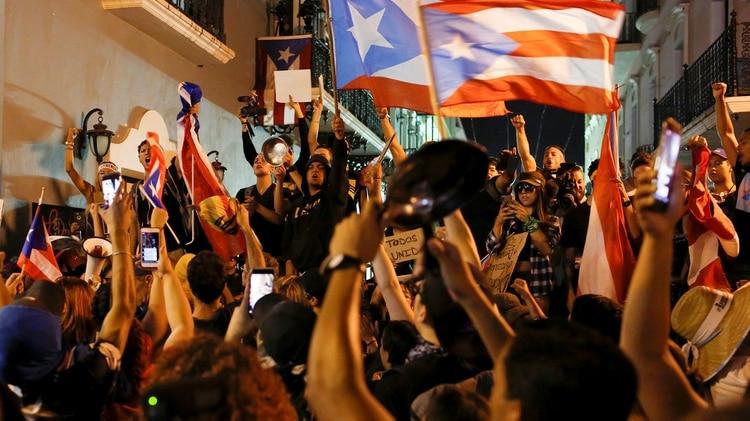 Manifestantes cantan y ondean banderas puertorriqueñas durante las protestas que pedían la renuncia del gobernador Ricardo Rosselló el 23 de julio de 2019 (REUTERS/Marco Bello)
