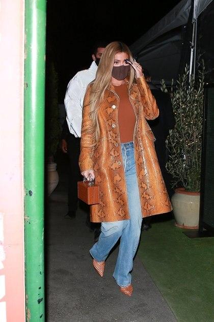 Kylie Jenner salió a comer con un grupo de amigas en Santa Mónica, California. La empresaria y diseñadora sorprendió con el look que eligió para el evento: lució un jean clarito, unos zapatos marrones en punta, un tapado de cuero del mismo color. La remera también era marrón, al igual que su cartera. Por su parte, llevó puesto su tapabocas y dejó ver el diseño que eligió para sus uñas: negras, largas y en punta (Fotos: The Grosby Group)