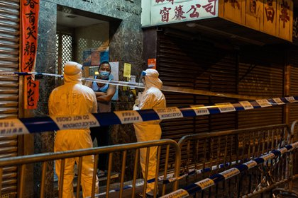 Government workers wearing personal protective equipment (PPE) talk to a resident in an area under lockdown in the Jordan area of Hong Kong, China, on Sunday, Jan. 24, 2021. Hong Kong imposed a temporary lockdown on thousands of residents for the first time to carry out mandatory testing of the coronavirus, with authorities warning the move will be repeated if needed to contain the outbreak. Photographer: Chan Long Hei/Bloomberg