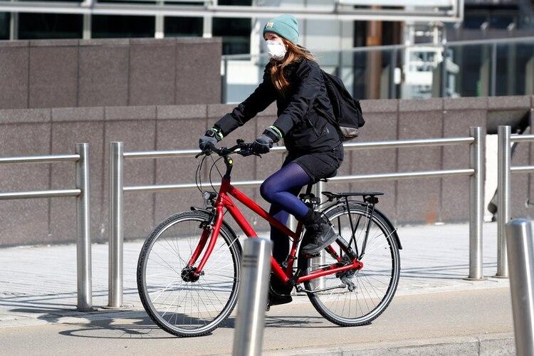 Una mujer usa una máscara facial protectora mientras monta en bicicleta en Bruselas, Bélgica, el 27 de marzo de 2020 (Reuters)