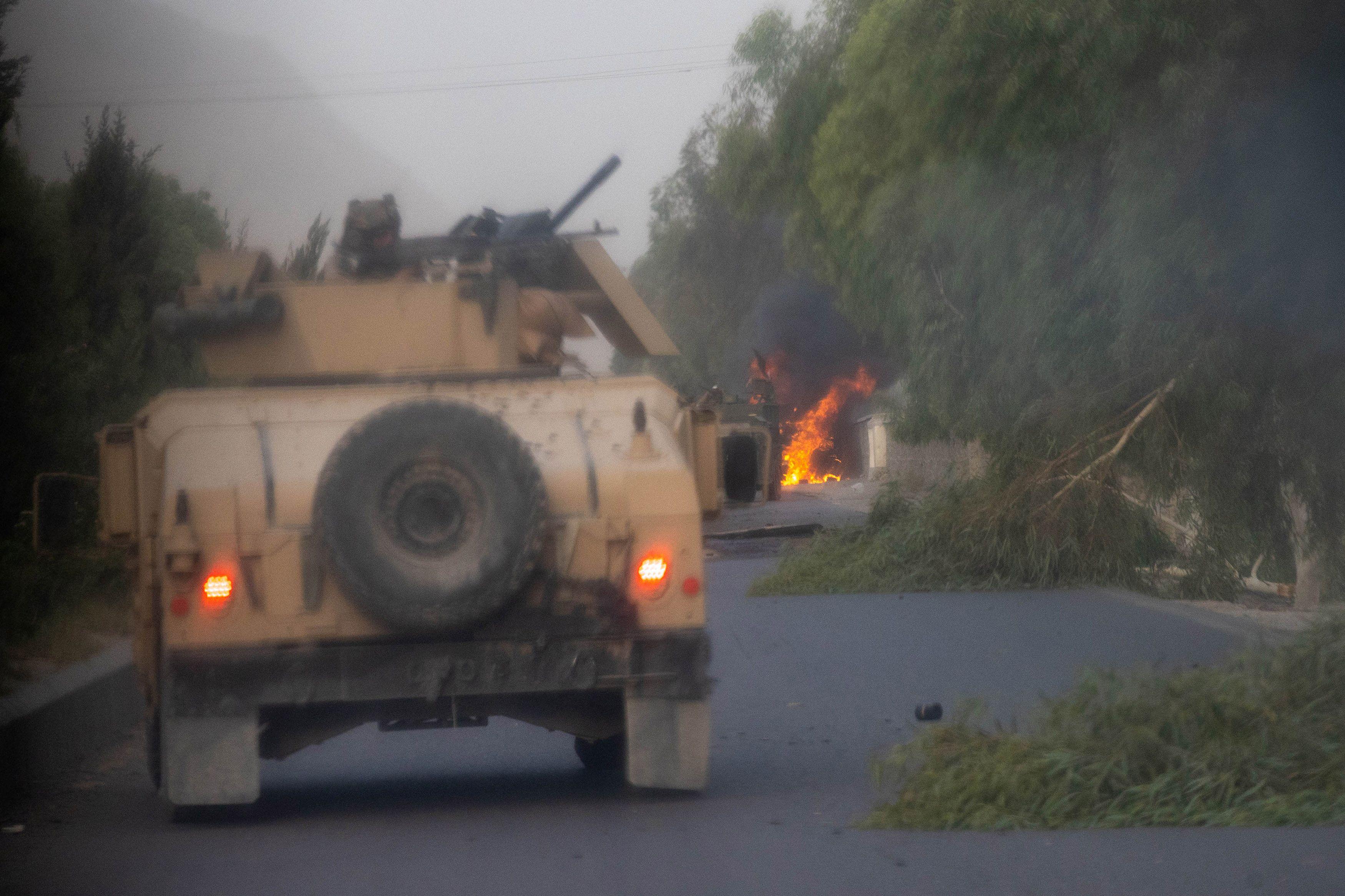 Humvees que pertenecen a las fuerzas especiales afganas se ven destruidos durante los fuertes enfrentamientos con los talibanes durante la misión de rescate de un oficial de policía asediado en un puesto de control, en la provincia de Kandahar, Afganistán, 13 de julio de 2021.
