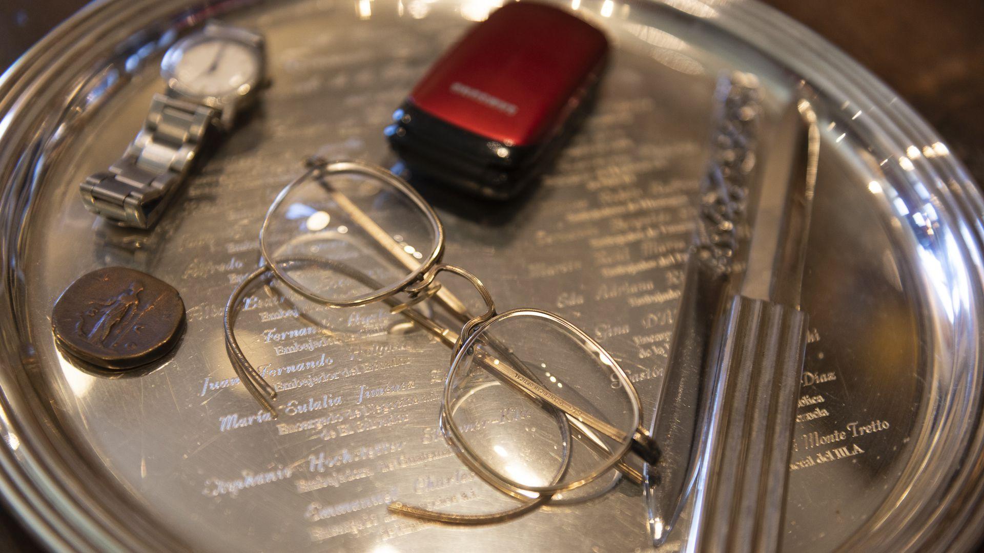 Los objetos personales de Torcuato Di Tella: sus característicos anteojos, un celular muy sencillo y su reloj