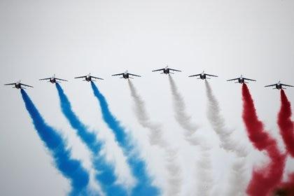 En el acto del martes, los aviones de combate que pintaron el cielo con humo azul, blanco y rojo volaron acompañados de los helicópteros que transportaron a pacientes de COVID-19 graves. (REUTERS/Benoit Tessier)