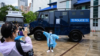 A young visitor poses in front of a police vehicle at the city's police college during an open day to celebrate the National Security Education Day in Hong Kong on April 15, 2021. (Photo by Anthony WALLACE / AFP)
