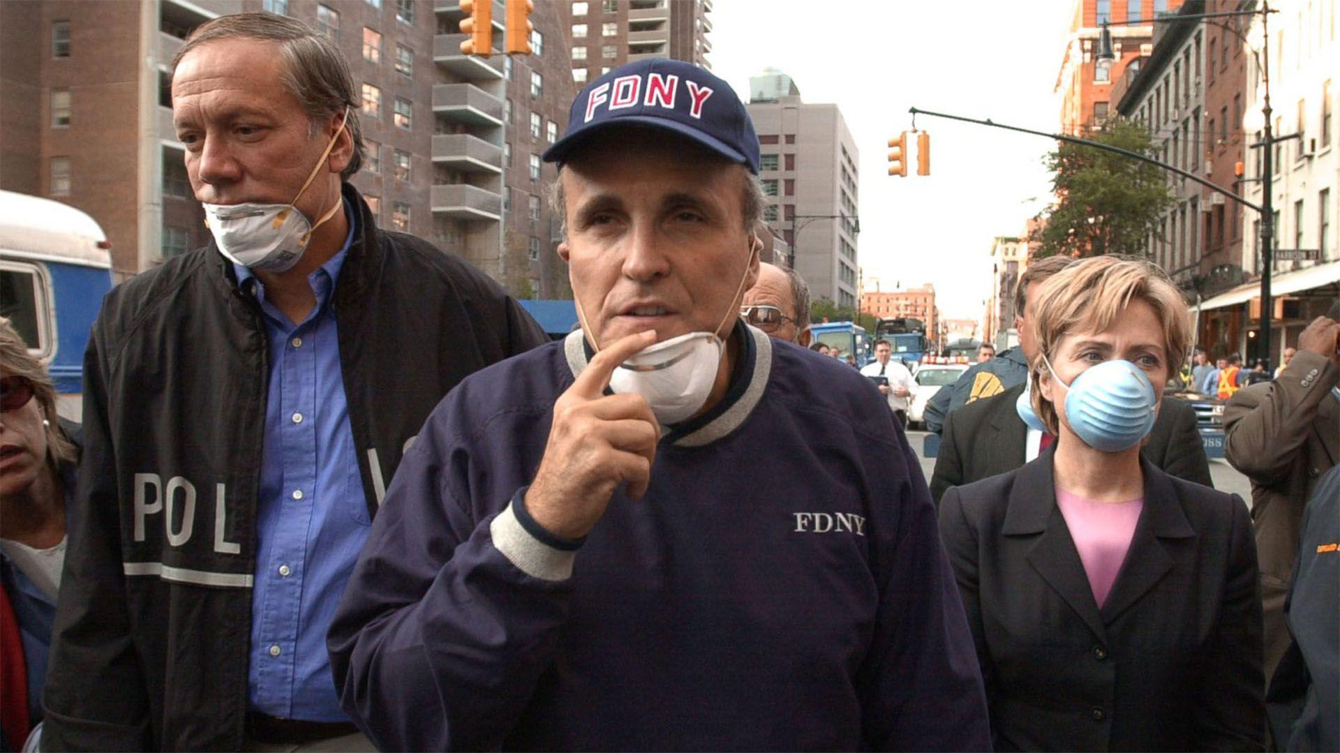 El ex alcalde de la ciudad de New York, Rudy Giuliani, recuerda que las llamas del 11 de septiembre permanecen aún con él todos los días, y que el trágico ataque representó lo peor y lo mejor de la humanidad. A su lado, una joven Hillary Clinton.