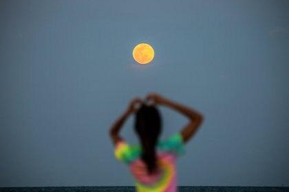 Una luna llena super rosa se ve de fondo mientras la gente se relaja en la playa de Miami Beach, el 26 de abril de 2021.(Photo by CHANDAN KHANNA / AFP)