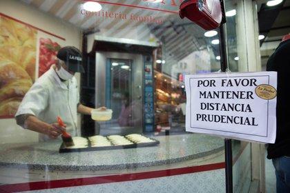 Un comerciante atiende con barbijo y a través de un cartel invita a respetar la distancia social