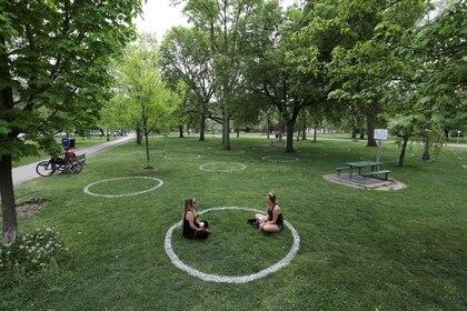 Dos mujeres se sientan en un campo donde se pintaron círculos para ayudar a los visitantes a mantener el distanciamiento social en el parque Trinity Bellwoods en Toronto, Ontario, el 28 de mayo de 2020 (REUTERS/Chris Helgren)